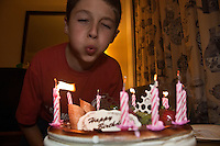 Ten year old boy blowing the candles out on his birthday cake.