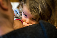 A mother comforts her daughter who is about two or three years old with a breastfeed at a sling meet held in the family restaurant and play area in a pub.