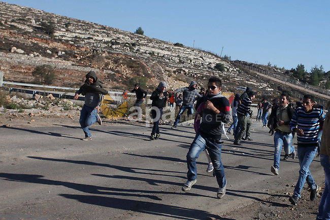 Palestinian demonstrators run cover from tear gas during clashes against Israel's operations in Gaza Strip, outside Ofer, an Israeli military prison near the West Bank city of Ramallah, Thursday, Nov. 15, 2012. Meanwhile, Palestinian President Mahmoud Abbas cut short a trip to Europe to deal with the crisis. Photo by Issam Rimawi