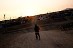 A man walks toward the road at sunset on Thursday, Apr. 16, 2009 in Ventanilla, Peru.
