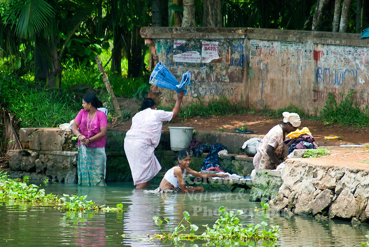 indian women washing clothes on backwaters of kerala in