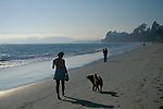 Woman walking dog on sand during day, Butterfly Beach, Santa Barbara, California