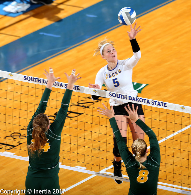 BROOKINGS, SD - SEPTEMBER 24: Hanna Jellema #5 from South Dakota State tips the ball past Erika Gelzinyte #14 and Bella Lien #8 from North Dakota State during their match Sunday evening at Frost Arena in Brookings. (Photo by Dave Eggen/Inertia)