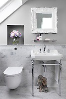 A wooden Buddha figure kneels beneath the sink in the bathroom clad with grey marble tiles