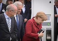 """Bundeskanzlerin Angela Merkel (CDU,r.) schaut sich am Montag (27.05.13) in Berlin waehrend einer Internationalen Konferenz"""" Elektromobilität bewegt"""" ein Ladekabel eines Elektroautos an,waehrend der Vorstandsvorsitzender der Daimler AG Dieter Zetsche (r.) und Bundesverkehrsminister Peter Ramsauer (CSU) daneben stehen. Foto: Timur Emek/CommonLens"""