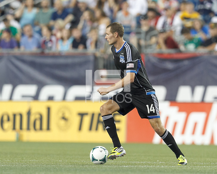 San Jose Earthquakes forward Adam Jahn (14) brings the ball forward.  In a Major League Soccer (MLS) match, the New England Revolution (white) defeated San Jose Earthquakes (black), 2-0, at Gillette Stadium on July 6, 2013.