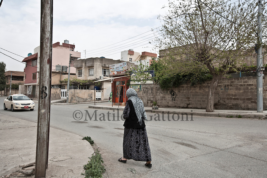 Iraq - Kurdistan - Sulaymaniyah -  A woman walking by a residential area in Sulaymaniyah city center.