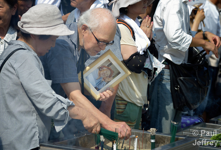 Bringing flowers and photos of their loved ones who have died from radiation poisoning, people pray on August 6, 2015, at a memorial in Hiroshima, Japan, that commemorates the victims of the atomic bombing of the city by the United States in 1945.