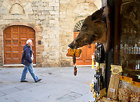 Michael McCollum.3/14/13.A man passes a shop featuring boar sausage in the town of San Gimignano, Tuscany, Italy.