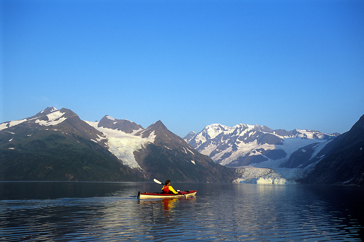 A sea kayaker paddles across Harriman Fjord toward Surprise Glacier at sunrise. The narrow piece of Pacific Ocean extends into the Chugach Mountains from Prince William Sound north of Whittier, Alaska.