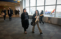 From left, Maggie Saucedo '22 and Madeline Martell '21 walk through Oakland International Airport.<br /> Eleven Occidental College first-years and sophomores traveled with Career Services staff and Senior Associate Dean of Students Erica O'Neal Howard to San Francisco for a day to visit Cambridge Associates, managers of Oxy's endowment, as part of their workforce diversity initiative. They were invited to meet with employees (including two alums), tour the office, and learn about careers in investment management. Students were able to see how their quantitative courses could be applied to future career opportunities.<br /> January 17, 2020.<br /> (Photo by Marc Campos, Occidental College Photographer)