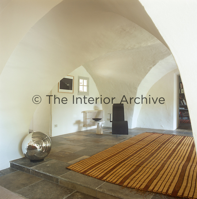 A connecting hallway with a painted vaulted ceiling and stone floor. Modern, contemporary furniture contrasts with the original, rustic features of the space.