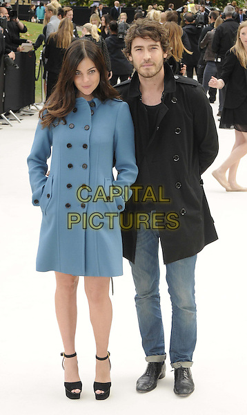 Julia Restoin Roitfeld & Robert Konjic.Burberry Prorsum Spring/Summer 2013 Womenswear Fashion Show, London Fashion Week LFW, Kensington Gardens, London, England..17th September 2012.full length black jacket jeans denim blue ankle strap peep toe shoes hands in pockets.CAP/CAN.©Can Nguyen/Capital Pictures.