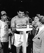 Heavyweight Champion Muhammad Ali stands on the scale during the weigh-in ceremony prior to his fifteen round heavyweight title fight against challenger Alfredo Evangelista of Spain at the Capitol Centre in Landover, Maryland on May 15, 1977.  Ali tipped the scales at 221 1/2 pounds.  Ali's purse will be $2.7 million and Evangelista will receive $85,000.<br /> Credit: Howard L. Sachs / CNP