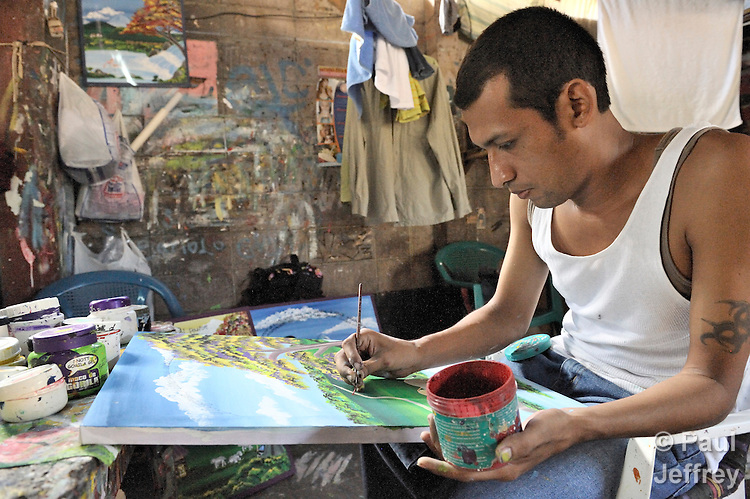 A prisoner paints a painting to earn money in a prison in Sensuntepeque, El Salvador.