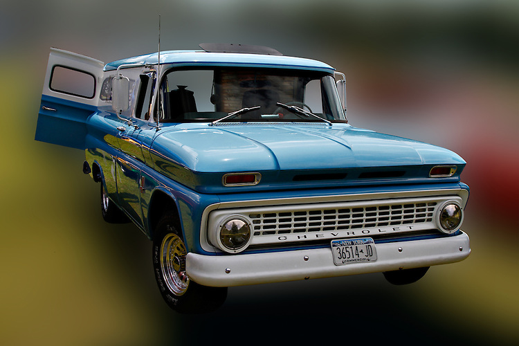 This 1963 panel truck was the last of the trucks bearing a wrap-around windshield. This beautiful blue and white truck with a sunroof and its back doors open stands alone with a blurred, multi-colored background camouflaging the environment at the 2010 Wings 'n' Wheels Showcase, Galway, New York.