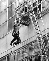 Man hangs from the fourth floor fire escape of Hastings Dept. store at 15th & Broadway in downton Oakland, California. Policeman grabs his wrist and deflected him as he fell into the thired floor fire escape below. Man was not seriously injured.  <br />