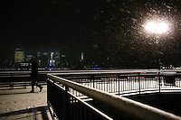 The lower Manhattan and the World Trade Center are seen while a man walks under the snow in Exchange Place, New Jersey, 01/17/2016 Photo by VIEWpress