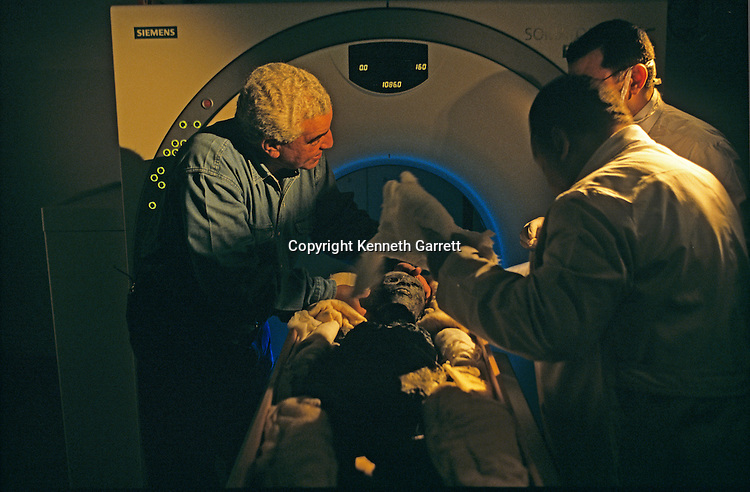 Archaeologist Zahi Hawass adjusts mummy of Tutankhamun before CT scan, Tutankhamun and the Golden Age of the Pharaohs, Page 266