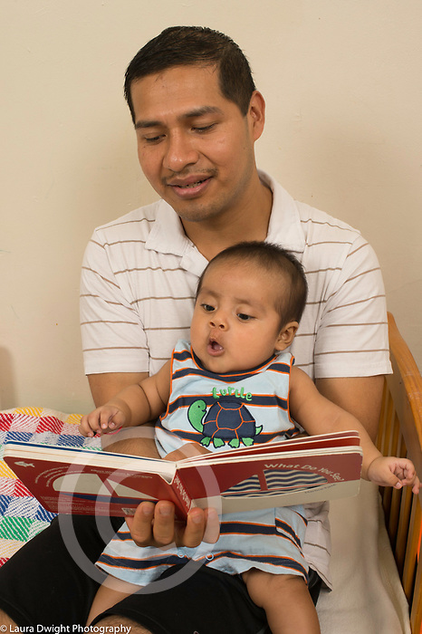 3 month old baby boy with father looking at board book interested expression on face