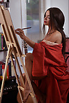 Artistic sensual portrait of a beautiful young woman fine artist painting in her home studio on an easel