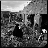 Al Qaouzah, South Lebanon, September 2006.A family in the rubble of their home; the neighboring orchards are littered with unexploded ordance: cluster bomb submunitions, shells and mortar shells.