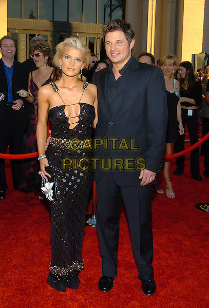 JESSICA SIMPSON & NICK LACHEY.32nd Annual American Music Awards held at the Shrine Auditorium. .14 November 2004.full length, black dress, plunging neckline, claevage, straps, celebrity couple, arried, husband, wife, pinstripe suit.www.capitalpictures.com.sales@capitalpictures.com.© Capital Pictures.