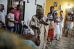 RIO DE JANEIRO, BRAZIL - JANUARY 24: Av&ocirc; de Santo, or spiritual grandfather, Luis de Omolu blesses a practitioner during a candomble ceremony, in Rio de Janeiro, Brazil, on Saturday, Jan. 23, 2015. Brazil's Afro-Brazilian religions which in recent years have come under increasing threats and prejudice, particularly from the growing number of evangelical churches. Candombl&eacute; originated in Salvador, Bahia at the beginning of the 19th century when enslaved Africans brought their beliefs with them. Umbanda and candombl&eacute; are Afro-Brazilian religions practiced in mostly Brazil. <br /> (Lianne Milton for the Washington Post)