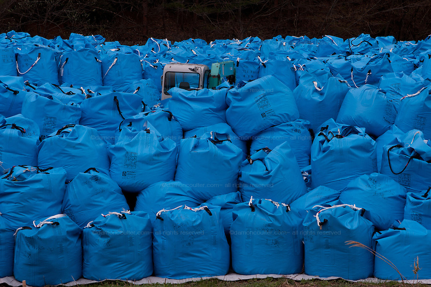 Topsoil, in blue vinyl bags, is stored in a field in the mountains near Nahara, Fukushima,  Japan. Tuesday April 30th 2013. The Japanese government has decided to remove the topsoil and vegetation from the areas affected by radiation after the disaster at Fukushima Daichi nuclear plant on March 11th 2011