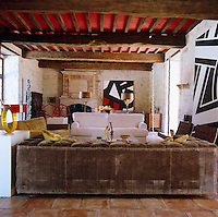 The large rustic living room is decorated with abstract paintings on the bare stone walls and a number of small sculptures