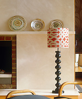 A red and white patterned shade on a standard lamp stands against the limestone partition wall in the living room