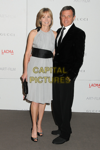Willow Bay & Robert A. Iger.The Inaugural Art and Film Gala held at LACMA in Los Angeles, California, USA..November 5th, 2011.full length  grey gray sleeveless dress black waistband clutch bag side married husband wife.CAP/ADM/BP.©Byron Purvis/AdMedia/Capital Pictures.