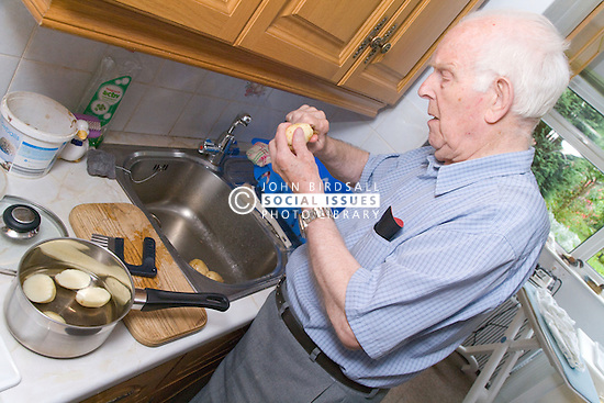 Elderly Carer who looks after wife; who has Alzheimer's disease; at home peeling potatoes at the kitchen sink,