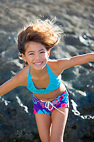 A young girl plays at a windy North Shore beach on O'ahu.