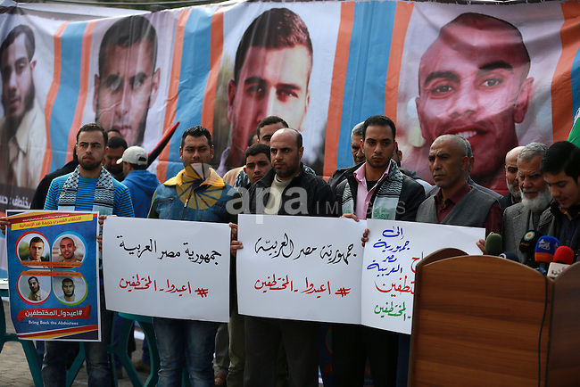 Relatives of four Palestinian men abducted by unidentified masked gunmen on August 19, hold their relatives' pictures during a protest demanding for their return, in front of the Egyptian embassy, in Gaza city, on February 27, 2016. Photo by Yasser Qudih