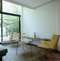A pair of string chairs by Alan Gould and a glass coffee table by Jason Maclean in the living area