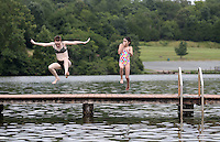 Ava Shurtleff and Rebekah Anderson jump off the dock at Chris Greene Lake in Albemarle County, VA. Photo/Andrew Shurtleff