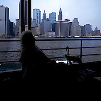 Lady sitting with walking stick on ferry.With the buildings of Manhattan in the background. New York, U.S.A circa 1975