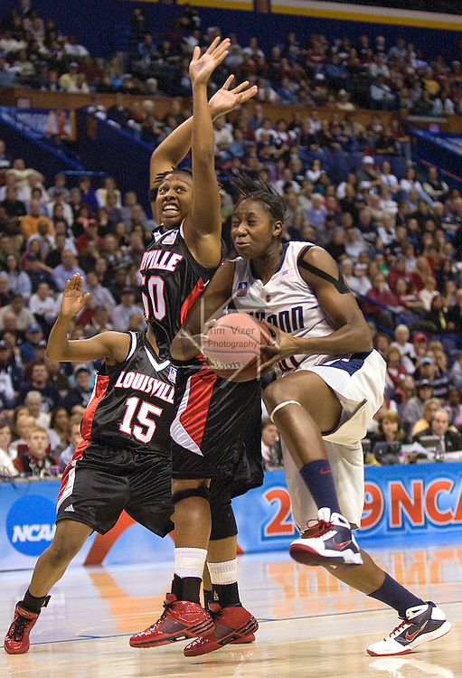 040709TVWOMENFINALFOUR3.UConn's Tina Charles (31, right) drives to the bucket as she's blocked at left by Louisville's Deseree Byrd (50) and at far left in background Tiera Stephen (15, partially hidden) at the NCAA Women's Final Four at the Scottrade Center in St. Louis, MO on Tuesday April 7, 2009..MCT/TIM VIZER