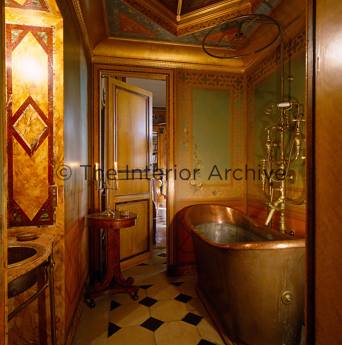 A French copper bath tub with elaborate brass taps and shower is surrounded by ornately painted and inlaid walls
