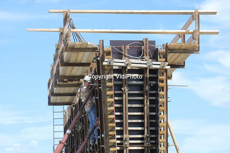 Foto: VidiPhoto..OCHTEN - Het geraamte voor het nieuwe viaduct over de A15 en de Betuwelijn bij Ochten begint vorm te krijgen. De komst van de Betuwelijn betekent dat er tal van provinciale wegen in het gebied omgeleid moeten worden. In onder meer Ochten wordt daarom gebouwd aan een viaduct dat zowel over de A15 als de Betuwelijn komt te liggen, zodat die op maaiveldhoogte kunnen blijven.