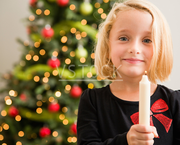 Girl (6-7) holding candlestick in front of Christmas tree