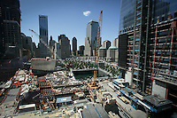 Tenth anniversary of 9/11.  Rebuilding at the World Trade Center site.  Footprint of the North Tower of the World Trade Center is part of the soon-to-be-completed 9/11 Memorial.  4 WTC is at left; 1 WTC is at right, both under-construction.  Photo by Ari Mintz.  8/11/2011.