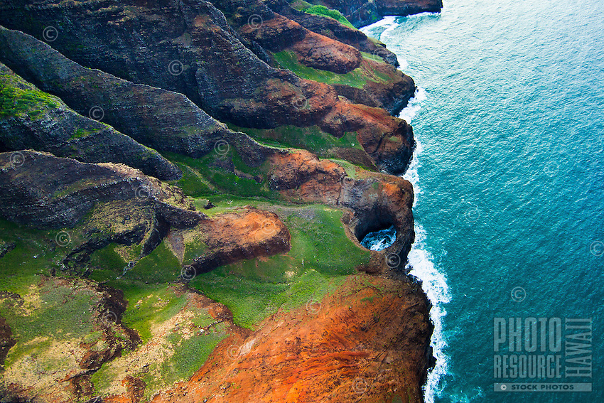 A perfect hole in the sea cliffs of Na Pali; green grass and red dirt complement the turquoise ocean.