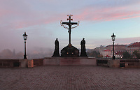 The Crucifix and Calvary sculpture, installed 1657, on the Charles Bridge or Karluv most over the Vltava river, Prague, Czech Republic. Bought in Dresden, this crucifix was originally made in 1629 by H Hillger after a design by W E Brohn. In 1861 the sandstone statues by Emanuel Max were added, portraying the Virgin Mary and John the Evangelist.<br /> The golden Hebrew text was added in 1696, when the Prague authorities accused a local Jewish leader, Elias Backoffen, of blasphemy. His punishment was to raise funds for gold-plated Hebrew letters, spelling out the Kedusha from a Hebrew prayer. The inscription was a symbolic humiliation of Prague Jews. The historic centre of Prague was declared a UNESCO World Heritage Site in 1992. Picture by Manuel Cohen