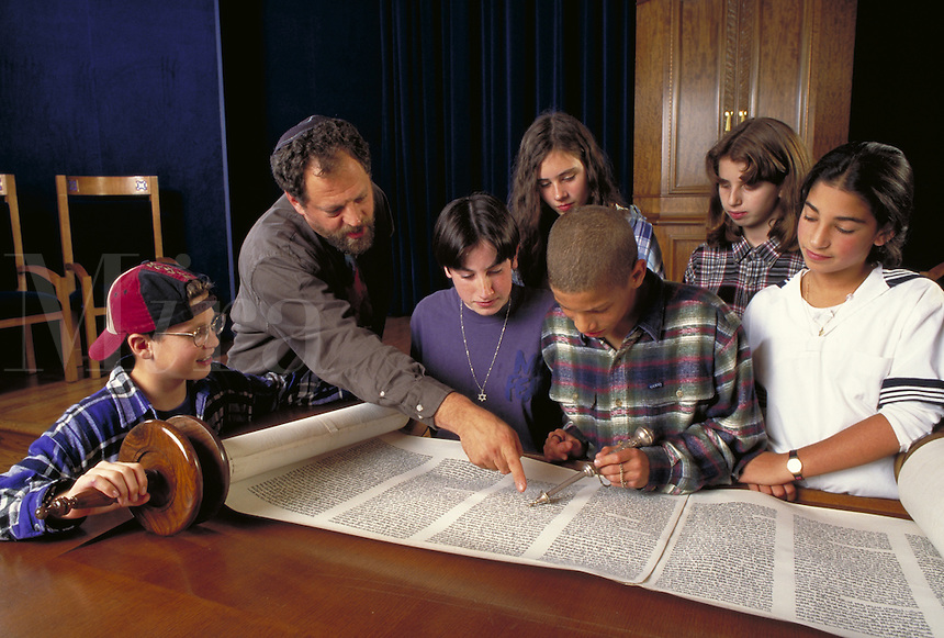 CLASS OF BAR MITZVAH STUDENTS WITH RABBI STUDYING TORAH IN SYNAGOGUE. BAR MITZVAH STUDENTS WITH TORAH IN SYNAGOGUE. SAN FRANCISCO CALIFORNIA.