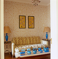 A pair of Chinese paintings depicting scenes of everyday life and a collection of blue opaline glass boxes displayed on a coffee table enhance this sitting room