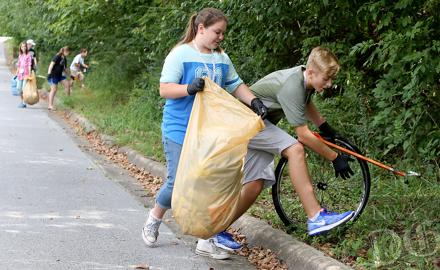 NWA Democrat-Gazette/DAVID GOTTSCHALK  Michael Morrison (right), an eighth grade student in the Fayetteville Virtual Academy, reaches down to collect a piece of trash as he works with Katie Palmer, a seventh grade student, Monday, August 28, 2017, and other students during a service learning project in the Walker Park area in Fayetteville. Fourth through eighth grade students from academy were participating in a weekly field experience. Once a month the weekly excursion participates in a service learning project. The week the students collaborated with the city of Fayetteville Parks and Recreation department on the cleanup.