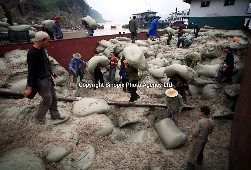 Laborers unload sacks of asbestos from a barge in Chongqing, China..