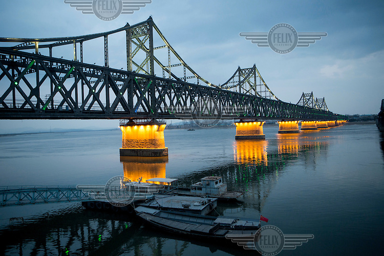 Lights illuminate the piers supporting the Sino-Korean Friendship Bridge that spans the Yalu River. It was originally built by the occupying Japanese between 1937 and 1943 and links the North Korean city of Sinuiju, on the far side, with the Chinese city of Dandong. /Felix Features